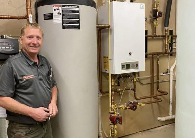 Lance standing next to the IBC high efficiency boiler and indirect fired water heater. The compact boiler is the heat source for the whole home and the domestic hot water.